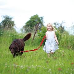 kleines Mädchen führt Hund spazieren