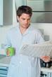 Junger Mann im Schlafanzug liest Zeitung