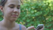 Teenage girl dialing number on smartphone in park outdoors