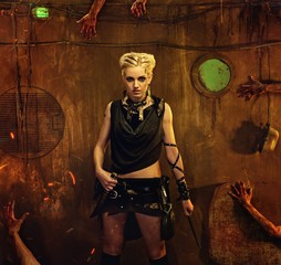 Woman in a bunker with zombie hands around her