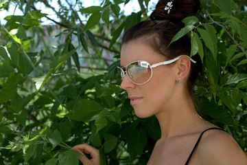 The beautiful girl in dark glasses against foliage