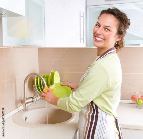 Dishwashing. Happy Young Woman Washing Dishes
