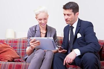 Mann und Frau arbeiten an Tablet Computer