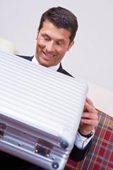 Geschäftsmann schaut erfreut in Koffer