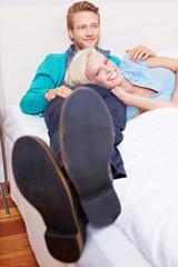 Junges Paar auf Bett in Hotelzimmer