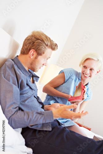 Frau zeigt Mann Schuhe nach Einkauf