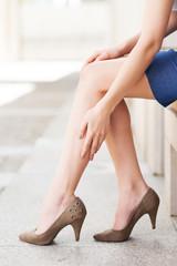 Woman in heels massaging tired legs