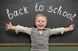 Cheerful smiling child stands at the blackboard. Looking at came