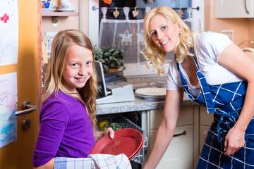 Hausfrau mit Tochter beim Geschirr abwaschen