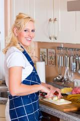 Junge Frau kocht und schneidet Zwiebel