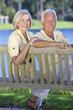 Senior Couple Sitting On Park Bench By Lake