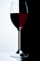Glass of red wine on a white and black background.