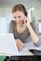 Young woman working from home with laptop and headset