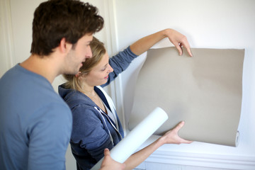 Young couple choosing color of all paper in new home