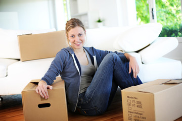 Young girl sitting by cardboards in new home