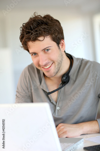 Student at home working with laptop and headset