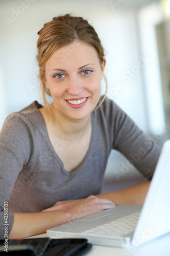 Beautiful young woman studying at home on laptop