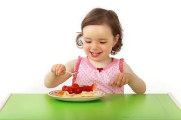 Mädchen isst ein Stück Erdbeerkuchen