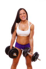Portrait of muscle woman posing in studio with dumbbells
