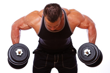 Portrait of strong man posing in gym with dumbbels