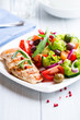 Grilled chicken fillet with fresh vegetables and olives