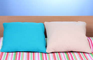bright pillows on bed on blue background