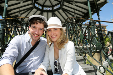 Romantic couple sitting by gazebo in touristic area