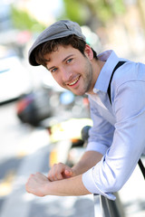 Portrait of young trendy guy standing outside