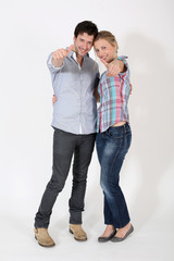 Young couple showing thumbs up on white background