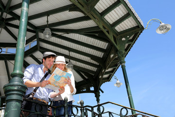 Young couple standing in gazebo reading touristic map
