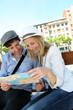 Young couple sitting on public bench to read touristic map