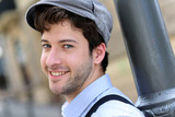 Closeup of young cheerful man wearing hat