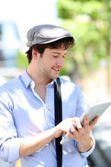 Young man with hat using digital tablet in town