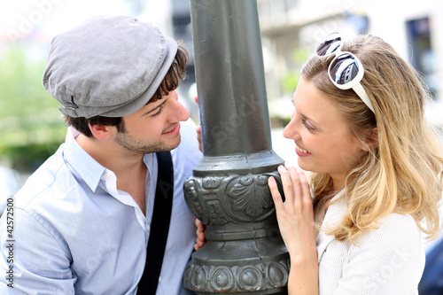 Portrait of cheerful couple standing by lamppost in town