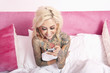 Naked woman with tattoo sitting in bed reading text message in mobile phone