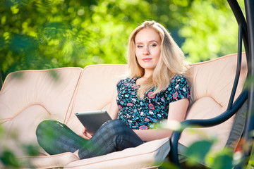 Positive beautiful young woman sitting outdoors in armchair seat