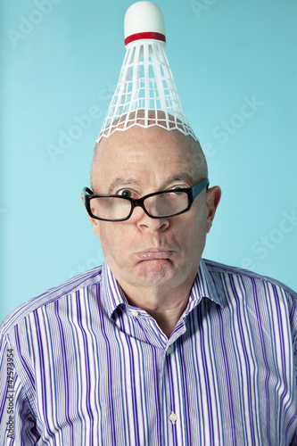 Portrait of senior man making face with shuttlecock on head