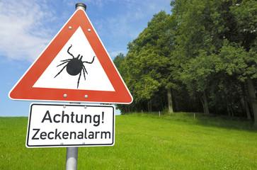 Schild Achtung! Zeckenalarm vor Wald und Wiese