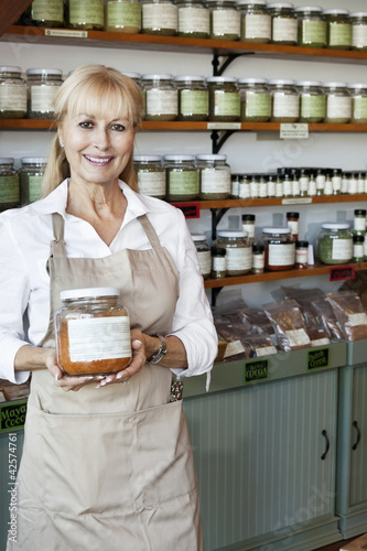 Portrait of a happy senior female employee holding spice jar in store
