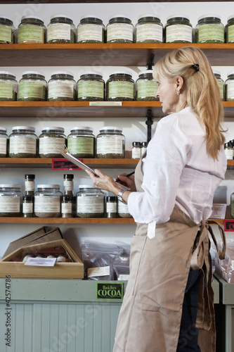 Side view of senior female employee going through list of spices in store