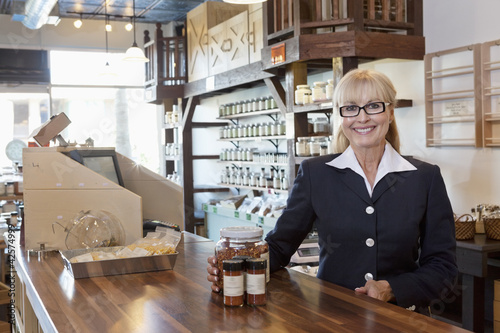 Portrait of a happy female owner standing at counter with spice jar in store