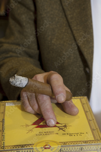 Cropped image of hands holding burning cigar