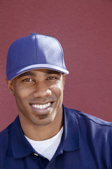 Portrait of a happy African American man with cap over colored background