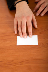 Female hand passing a blank greeting card on a wooden desk