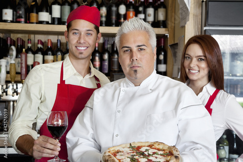 Portrait of a confident chef holding pizza with wait staff in background