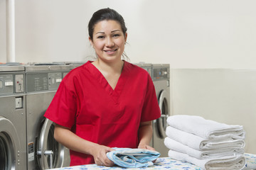 Portrait of a happy woman in red uniform with towel in Laundromat