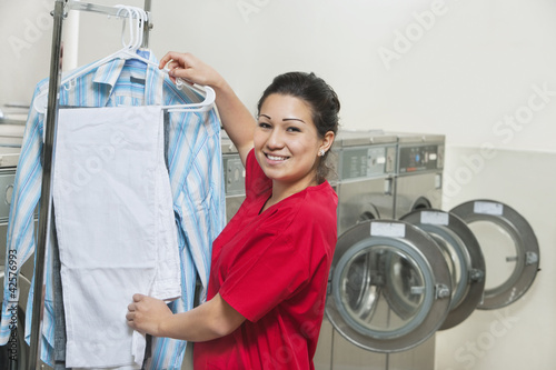 Portrait of a happy young woman drying clothes in Laundromat