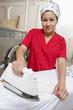 Portrait of a female employee wearing bandana while ironing in Laundromat
