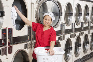 Portrait of a happy young female employee putting clothes in washer