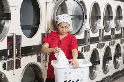 Young female employee carrying laundry basket with washing machines in background